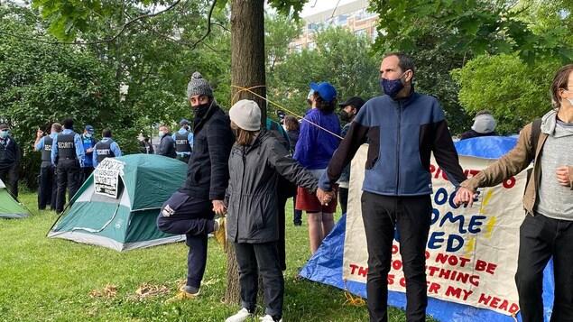 Une dizaine de personnes se tiennent par la main autour d'une tente.