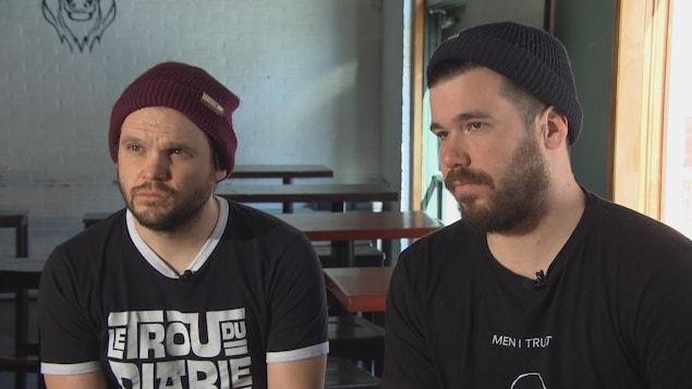 Deux hommes vêtus de vêtements foncés sont assis sur des tabourets lors d'une entrevue.
