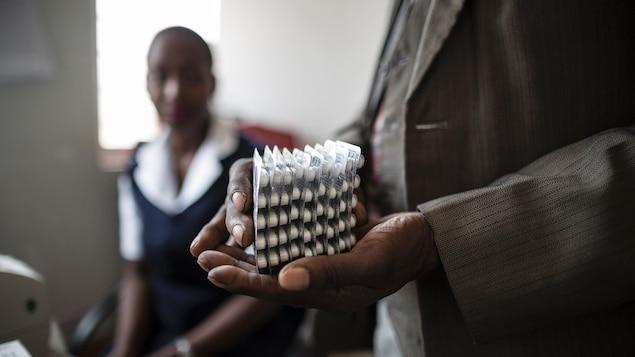 Un homme tient des cartons de pilules.