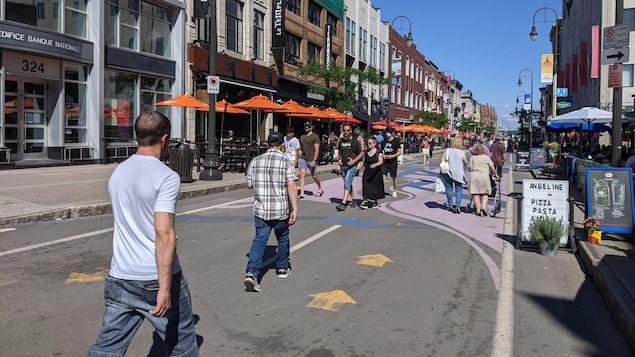 Des gens marchent en direction de la promenade portuaire.