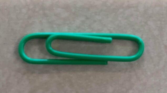 Une pince à papier verte sur un bureau.