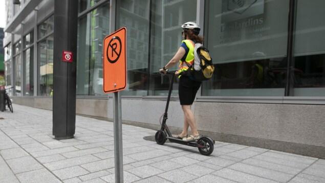 Une femme utilise une trottinette électrique sur le trottoir.
