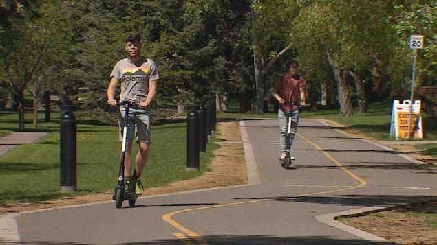 Deux hommes, chacun sur leur trottinette, circulent sur une piste cyclable.