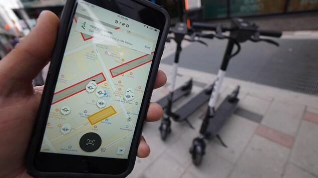 Une main tient un téléphone intelligent sur lequel est affiché une carte.
