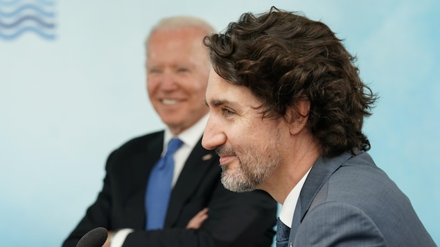 Justin Trudeau avec Joe Biden en arrière-plan.