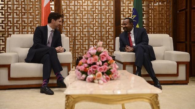 Justin Trudeau et Abiy Ahmed assis côte à côte, se parlant.