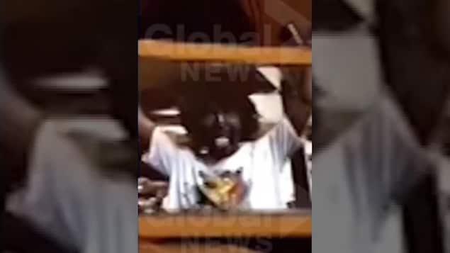 Justin Trudeau le visage maquillé en brun, les bras dans les airs et la bouche ouverte.