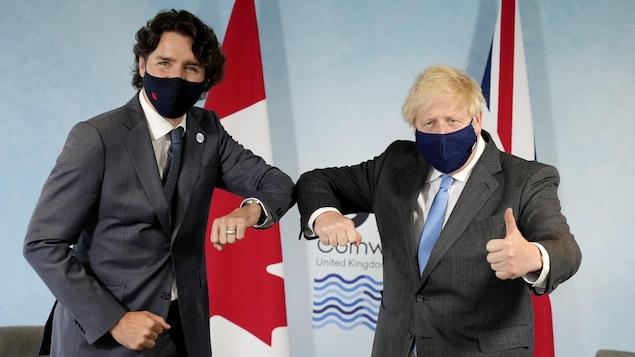 """2021 年 6 月 11 日,星期五,加拿大總理賈斯汀·特魯多 (Justin Trudeau) 在英國西南部海濱村莊卡比斯灣 (Carbis Bay) 的 G7 峰會上與英國首相鮑里斯·約翰遜 (Boris Johnson) """"碰肘""""。"""