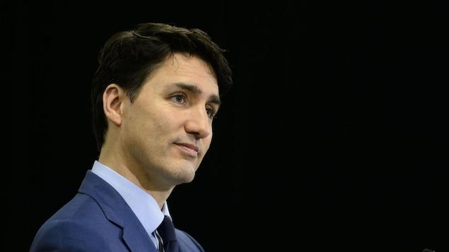 Justin Trudeau tient un micro tout en fixant des yeux.