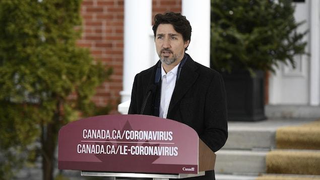 Plan moyen de Justin Trudeau derrière un micro, répondant à des questions.