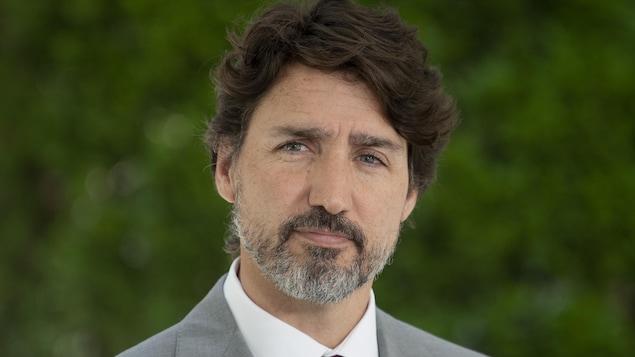 Justin Trudeau porte un complet gris avec une cravate violette, lors de sa conférence de presse devant sa résidence à Rideau Cottage, à Ottawa.