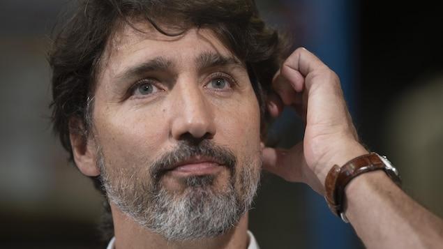 Justin Trudeau portant la main à son oreille.