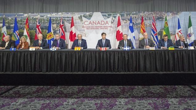 Plusieurs personnes sont assises à une même longue table devant les drapeaux des différentes provinces et territoires canadiens lors d'une conférence de presse.