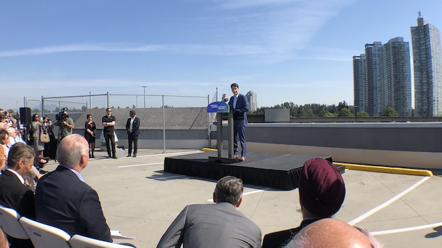 deux personnes regardent Justin Trudeau un peu plus loin, qui se tient derrièere un lutrin sur une scène. En arrière-plan, une tour à condo.