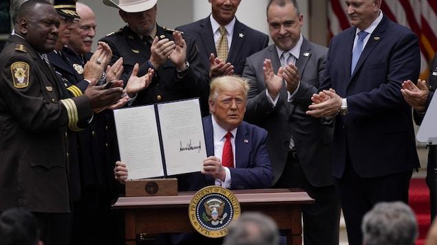 Donald Trump tient un décret dans ses mains et est applaudi par plusieurs personnes qui l'entourent.