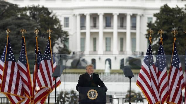 Donald Trump debout derrière un lutrin.