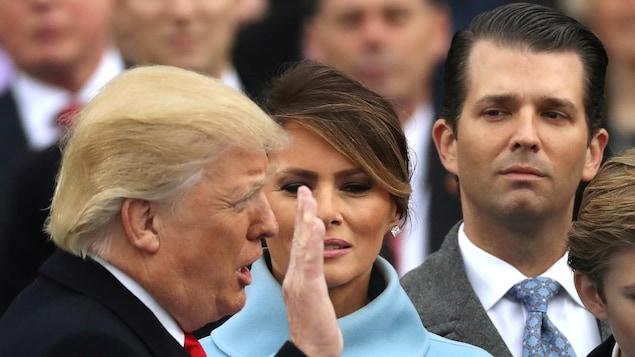 Donald Trump fils regarde son père, qui a la main levée et est à côté de Melania Trump, prêter serment.