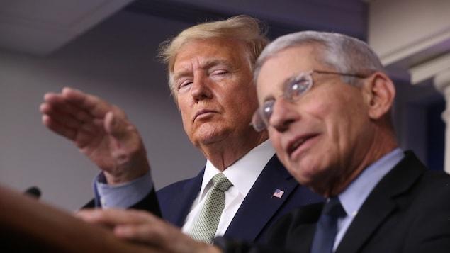 Les yeux mi-clos, Donald Trump regarde le Dr Anthony Fauci, qui a le bras levé, au cours d'une conférence de presse.