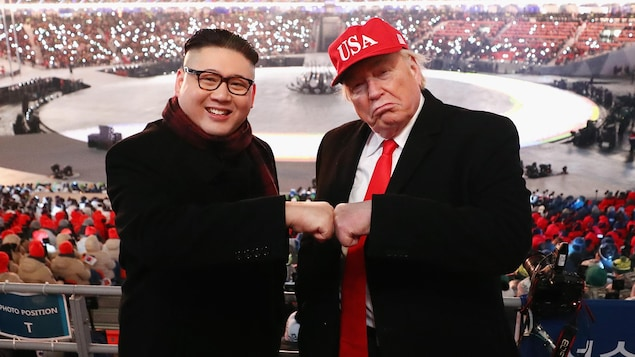 Des sosies des présidents Kim et Trump joignent leurs poings fermés, dans les estrades du stade où se déroule la cérémonie.