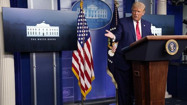 Donald Trump, au podium, regarde un de ses conseillers pendant sa conférence de presse à la Maison-Blanche.