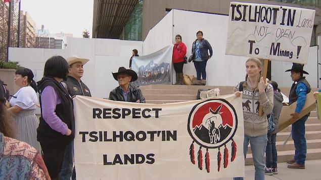 """Des gens portent des pancartes qui disent """"Respectez les terres Tsilqotin"""" et """"Les terres Tsilquot'in ne sont pas ouvertes aux minières""""."""