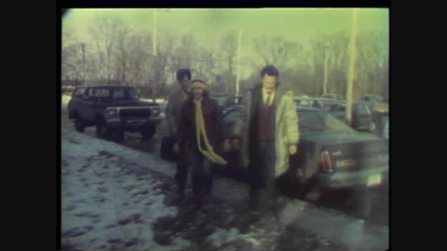 Trois hommes descendent d'une voiture, dans les années 80.