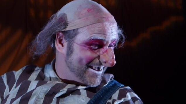 un homme déguisé en clown sourit.
