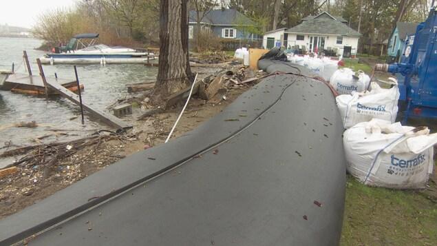 Large tube rempli d'eau qui bloque la montée des eaux sur les rives des îles de Toronto.