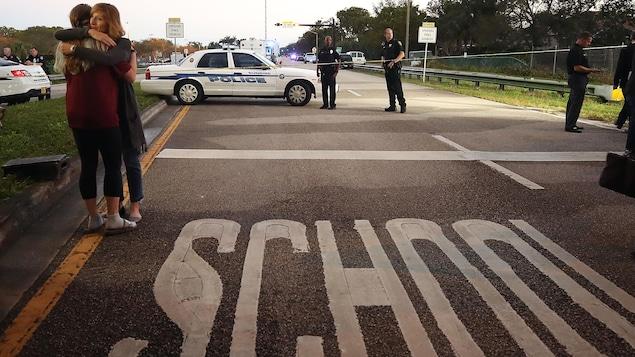 Deux femmes s'enlacent, près d'une voiture de police et de deux policiers. L'inscription «École» apparaît sur la chaussée.