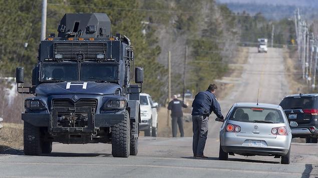 Un blindé de la police sur la route et des policiers qui interceptent des automobilistes.