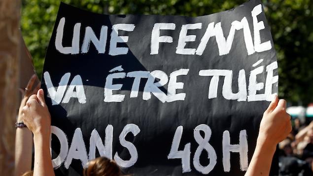 une personne porte une pancarte où il est écrit « une femme va être tuée dans 48 heures »