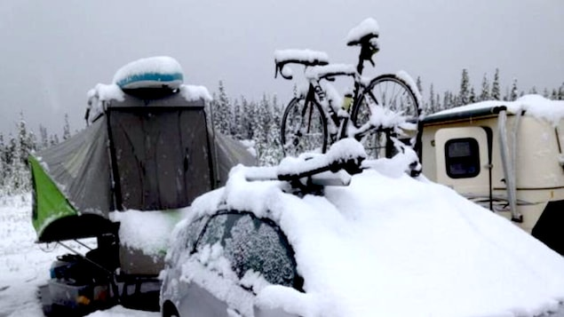 La neige épaisse recouvre une voiture avec un vélo sur le toit