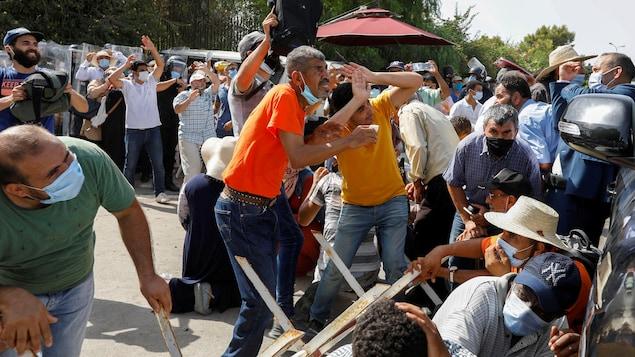 Des Tunisiens tentent d'éviter des projectiles devant le parlement à Tunis.