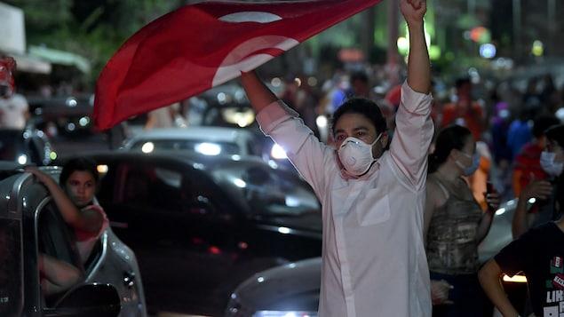Un jeune homme brandit un drapeau tunisien dans une foule de piétons et de véhicules.