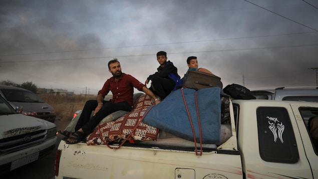 Des gens fuyant la ville de Ras al Ain sont assis sur leurs effets personnels à l'arrière d'un camion.