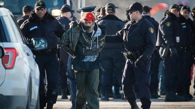 Des policiers accompagnent un homme menotté