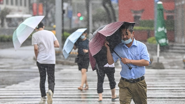 Un homme tente de tenir son parapluie, qui se ploie sous le torrent de la pluie.