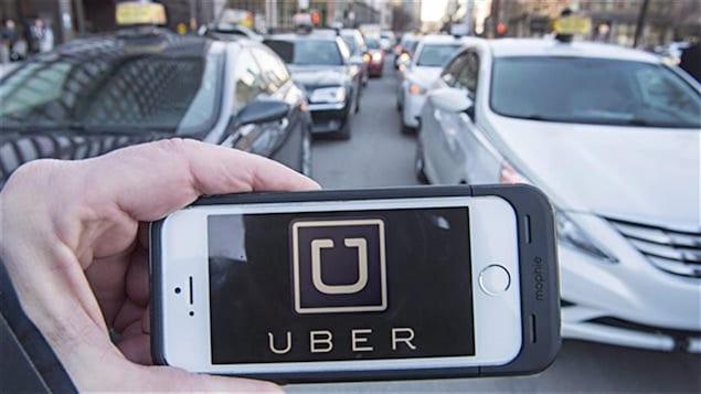 Un homme tient un téléphone intelligent avec l'application d'Uber devant des voitures de taxi.