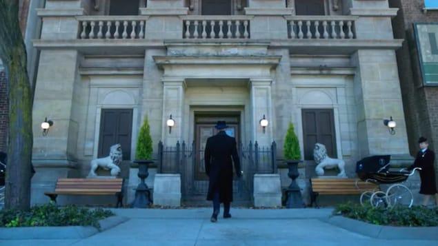 Un homme, vu de dos, marche vers un grand bâtiment d'époque.