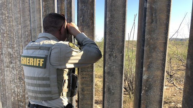 Un policier observe à travers la clôture qui sépare les États-Unis du Mexique