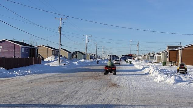 Rue de la communauté innue de Unamen Shipu en hiver. Un véhicule tout terrain roule.