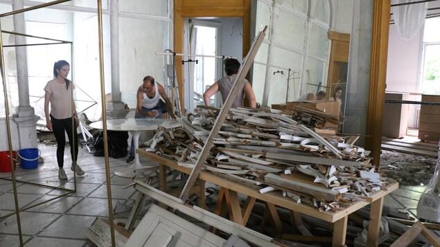 Des gens travaillent dans une maison où est posé un amas de débris.