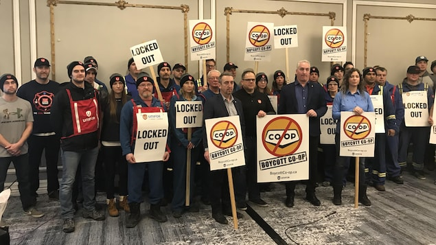 Des employés de la raffinerie debout dans la salle d'un hôtel tiennent des pancartes réclamant le boycottage des magasins du réseau Co-op.