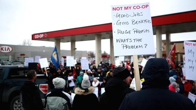 Des personnes manifestent à l'extérieur tout près d'une station-service Co-op.