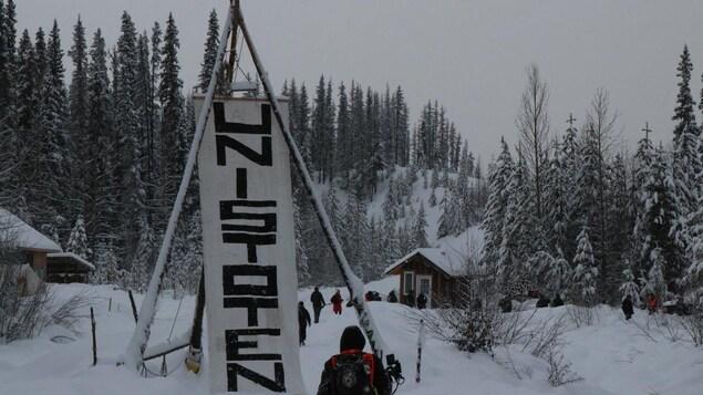 Un paysage enneigé avec une affiche Unistoten dressée au centre d'un tipi en bois.