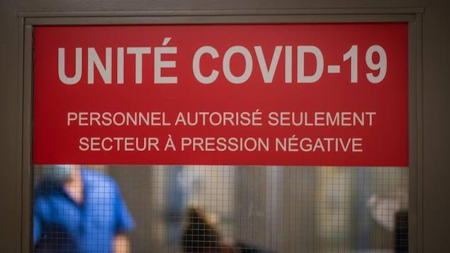 Une affiche Unité COVID-19 sur les portes-battantes dans un hôpital.