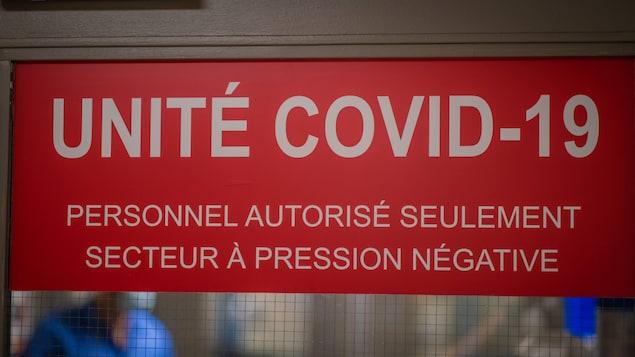 Une affiche sur la porte battante d'un hôpital annonçant Unité COVID-19.