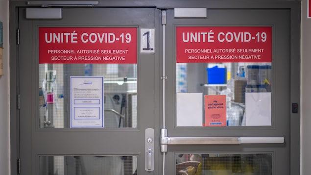 Des portes battantes dans un hôpital indiquant Unité COVID-19.