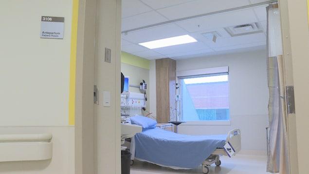 Vue de l'intérieur d'un chambre d'hôpital, meublée d'un lit. Un panneau indique à l'entrée qu'il s'agit d'une chambre de traitement pré-accouchement.