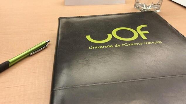 Un bloc-note noir avec le logo de l'UOF est posé sur un bureau.